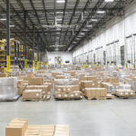 large distribution center with industrial fan, pallets of product, and loading dock