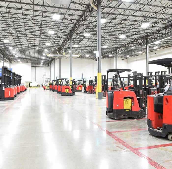 large warehouse with forklifts being parked and charging