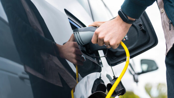 man plugging into electric vehicle
