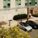 row of EV charging stations with electric vehicles